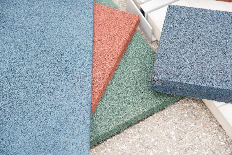Revestimiento de suelos moderno bajo la forma de tejas de goma del rojo, verdes fotos de archivo libres de regalías