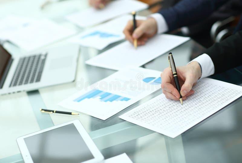 Revidera begreppet på att arbeta med plan och analysering av investeringdiagram på arbetsplatsen arkivfoto