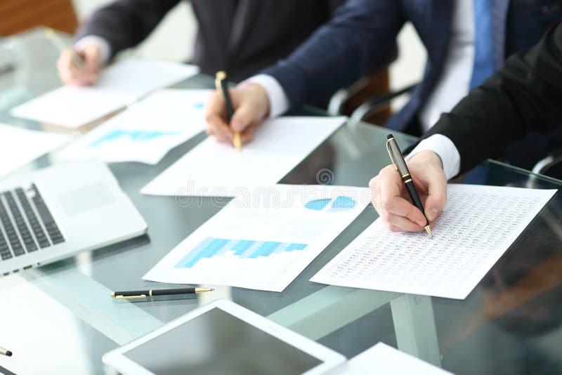 Revidera begreppet på att arbeta med plan och analysering av investeringdiagram på arbetsplatsen fotografering för bildbyråer