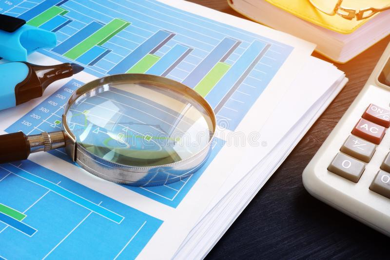 revidera Förstoringsglas på finansiella dokument med grafer ljudbandet royaltyfria bilder