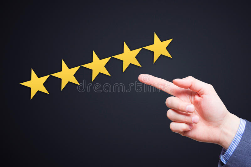 Review, increase rating or ranking, evaluation and classification concept. Businessman pointing on five yellow stars to increase stock photography