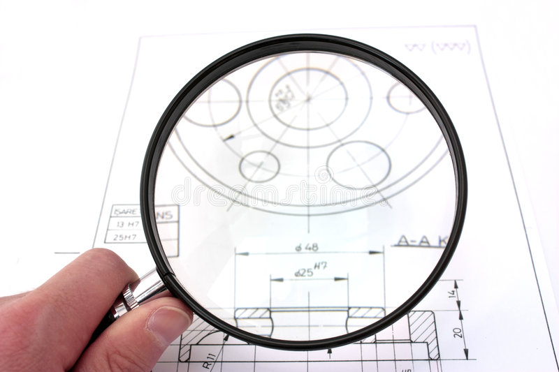Reviewing technical drawing. Focus on magnifier. royalty free stock photo