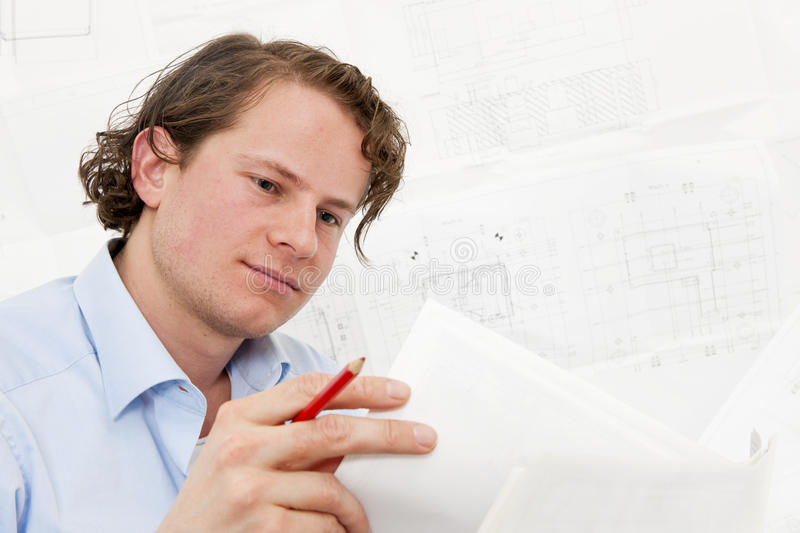 Reviewing technical drawings. Young engineer reviewing a stack of technical drawings, with more complex designs in the background stock photography