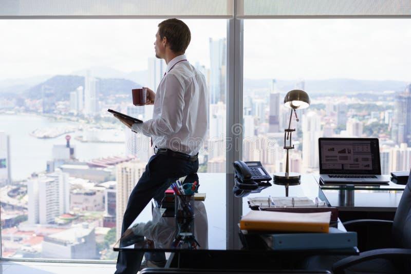 Revisão da imprensa da notícia da leitura do homem de negócio no PC da tabuleta fotos de stock royalty free