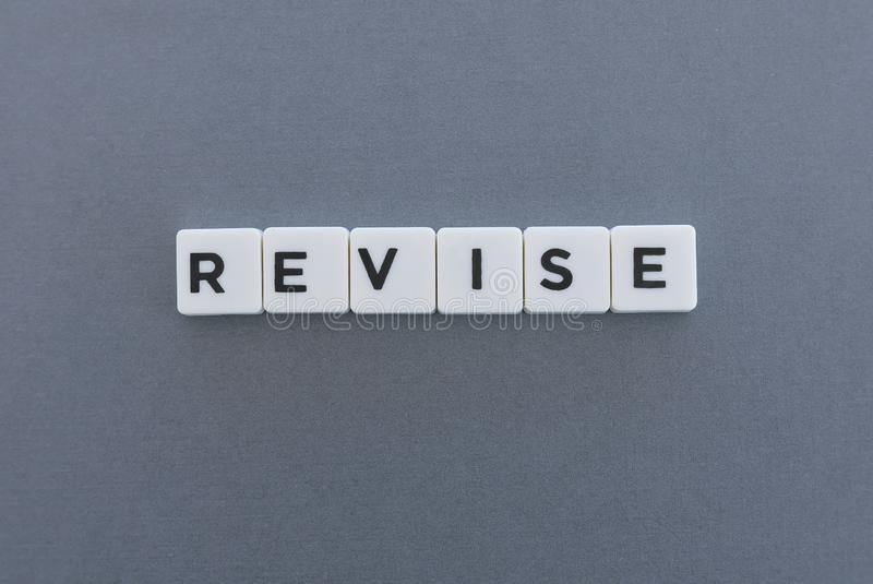 Revise word made of square letter word on grey background. Check review text dictionary revision business evaluation analysis inspection definition reference stock photo