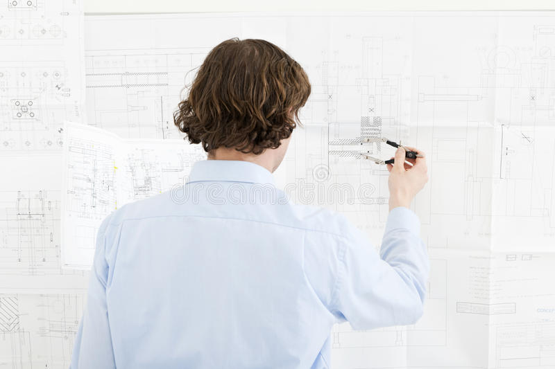 Revisions of a technical drawing. Engineer going over the revisions of a complex technical drawing stock image