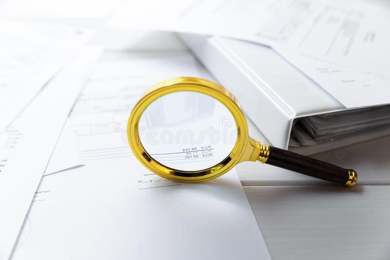 Revisionsbegrepp - förstoringsglas- och affärsdokument royaltyfria bilder