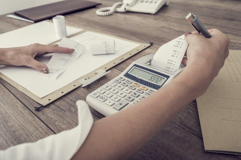 Revisor eller affärskvinna som balanserar böckerna arkivfoto