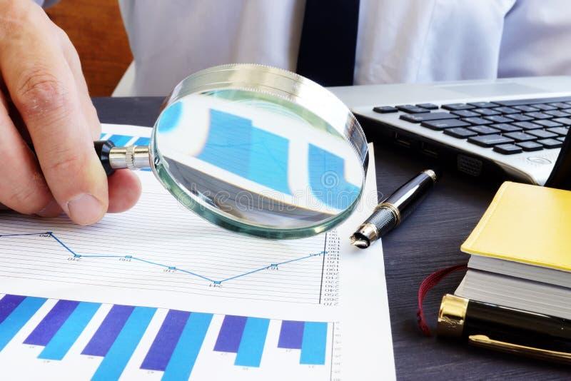 Revisor med förstoringsglaset som kontrollerar den finansiella rapporten arkivbilder