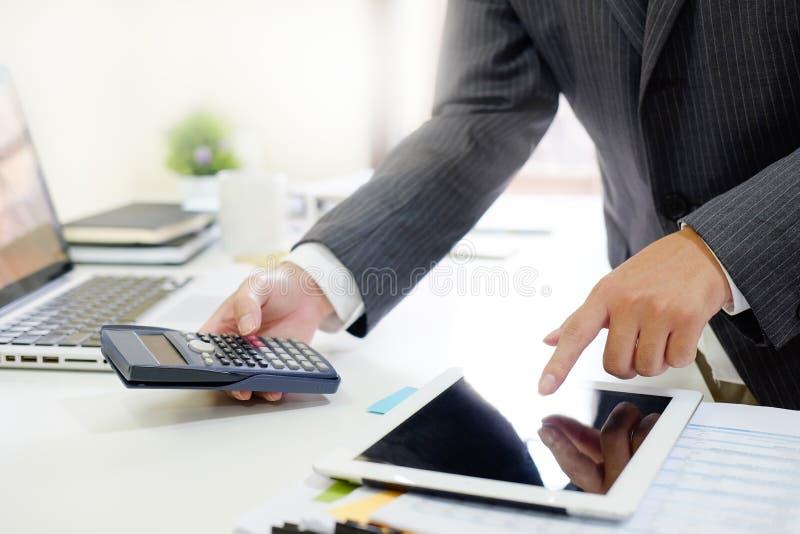 Revisor oficial de contas, homem que trabalha na tabuleta co do smartphone fotos de stock