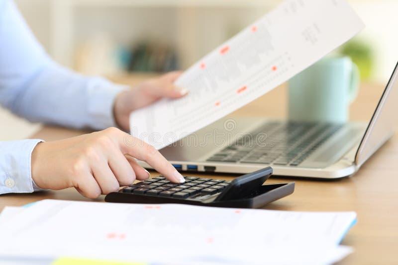 Revisor som beräknar med en räknemaskin på ett skrivbord royaltyfri fotografi