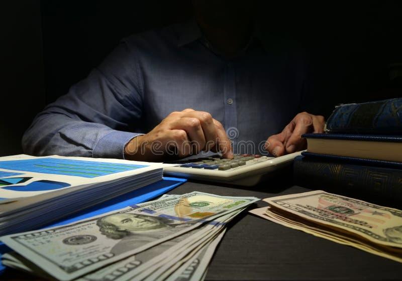 Revisorn använder räknemaskinen för att räkna för pengar Unsecured personligt lån royaltyfri foto