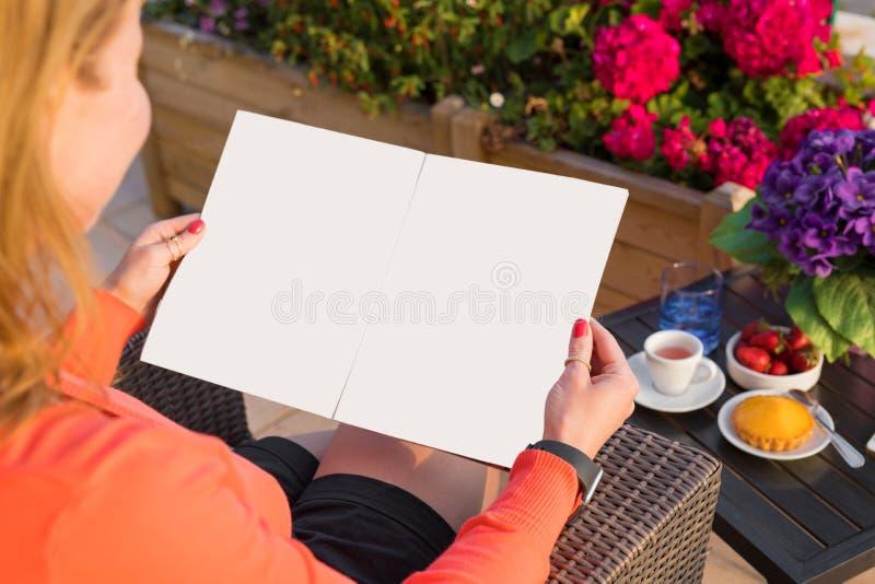 Revista de la muestra de la lectura de la mujer, maqueta vacía para sus los propio diseño foto de archivo libre de regalías