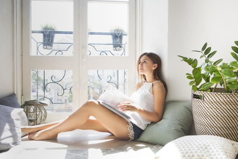 Revista de moda bonita joven de la lectura de la muchacha cerca de la ventana foto de archivo