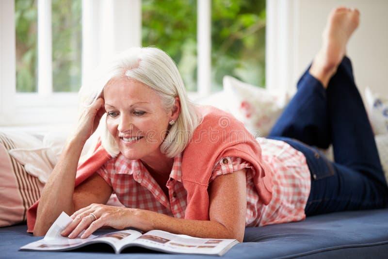 Revista envejecida centro de la lectura de la mujer que miente en el sofá imagen de archivo libre de regalías