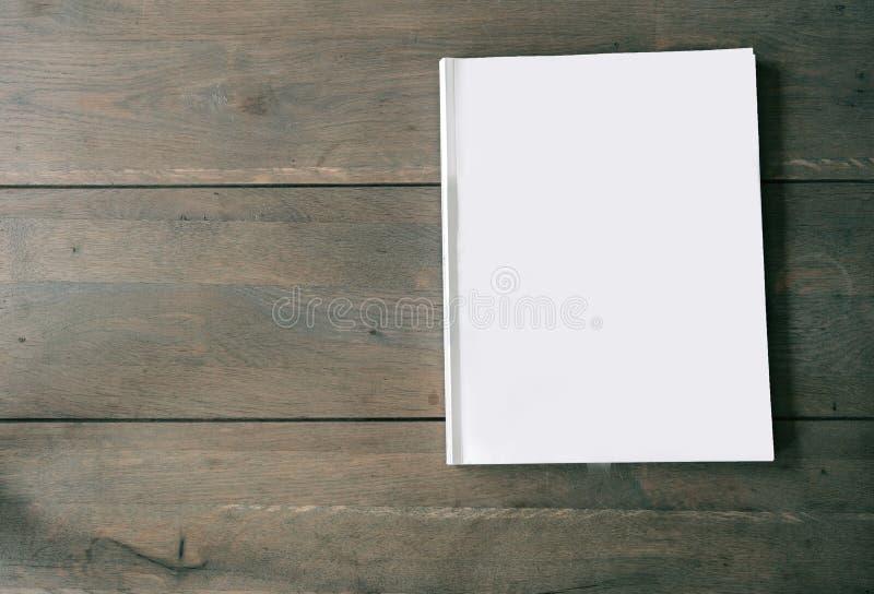 Revista o folleto en blanco sobre textura de madera del fondo, la visión superior y el espacio para el emplate del texto para su  foto de archivo