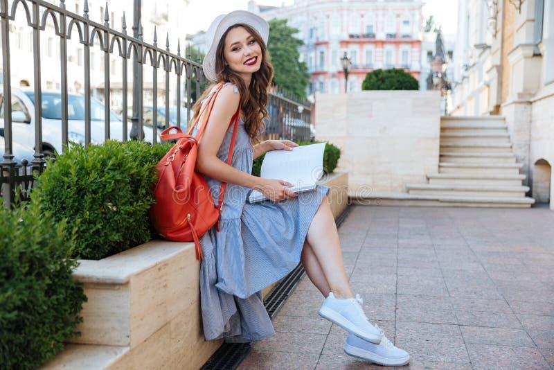 Revista sonriente de la sentada y de la lectura de la mujer joven en la ciudad imagen de archivo libre de regalías