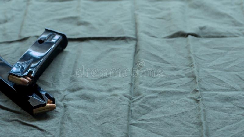 Revistas de acero negras de la pistola de la arma de mano cargadas con la munición hueco del punto, descansando en un fondo del p imagen de archivo