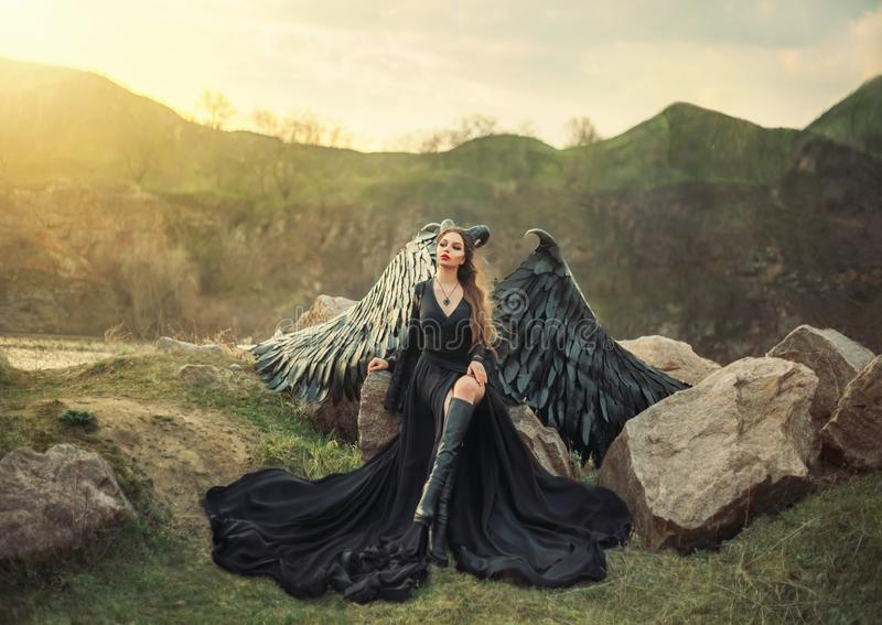 Revived gargoyle, queen of night watching sunrise, girl in long light black dress with black feather wings sits on rocks stock photos