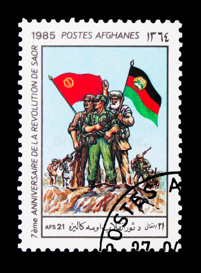 Revolutionaries with Flags, Seventh Anniversary of the Sawr Revolution serie, circa 1985. MOSCOW, RUSSIA - DECEMBER 21, 2017: A stamp printed in Afghanistan stock images