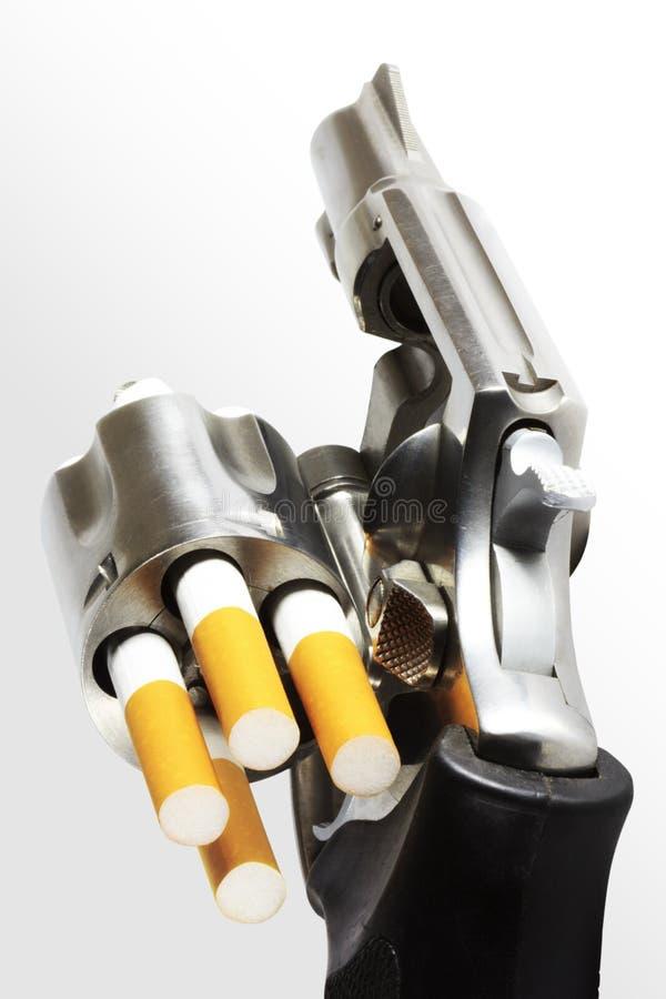 Revolver avec des remboursements in fine de cigarette (chemin de découpage) photo stock