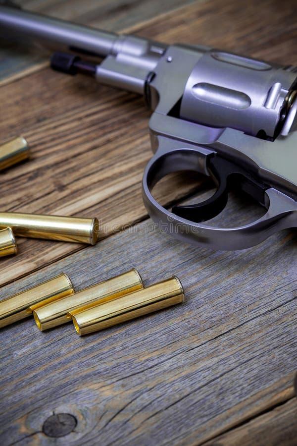 Revolver de Nagan avec des cartouches sur les conseils en bois photographie stock