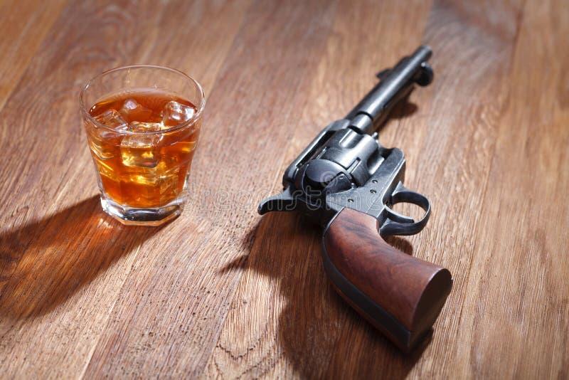 Revolver et munitions occidentaux sauvages avec le verre de whiskey et de glace sur la table en bois photos libres de droits