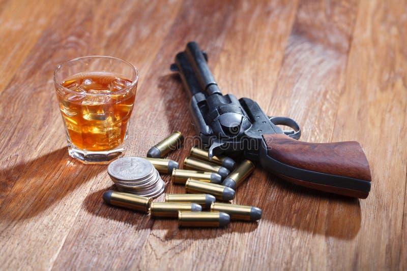 Revolver et munitions occidentaux sauvages avec le verre de whiskey et de glace avec le vieux dollar en argent sur la table en bo image stock