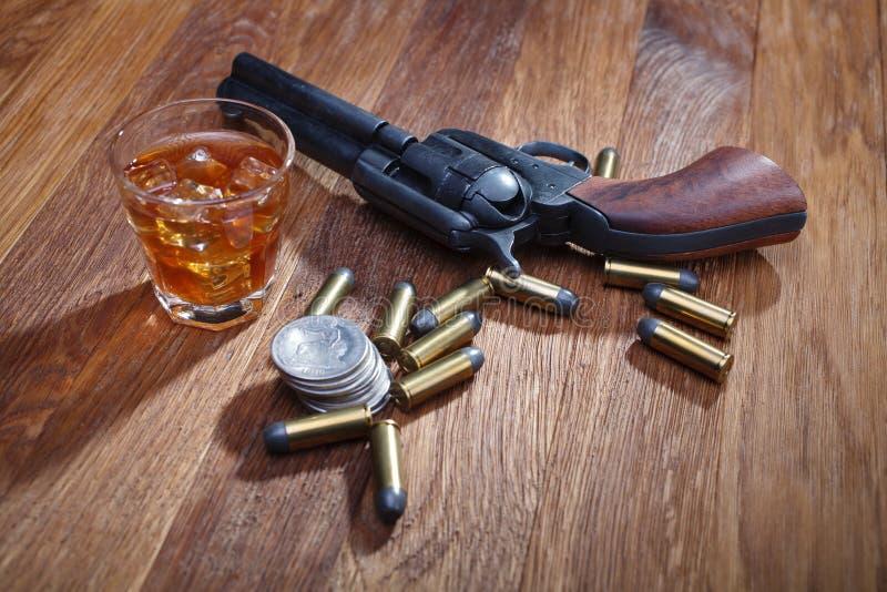 Revolver et munitions occidentaux sauvages avec le verre de whiskey et de glace avec le vieux dollar en argent sur la table en bo photo libre de droits