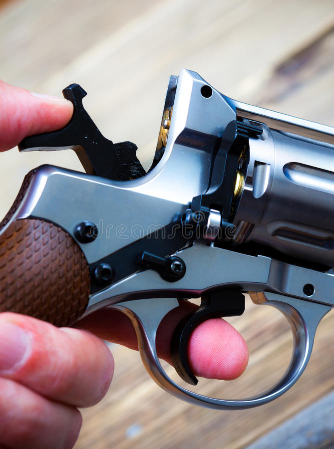 Revolver with the hammer cocked in his hand royalty free stock photography