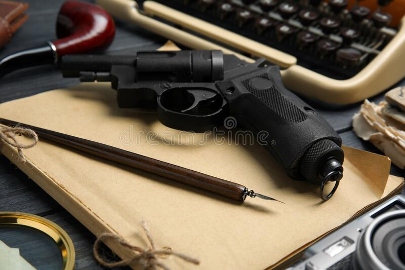 Revolver, ink pen and vintage notebook on wooden table, closeup. Detective`s workplace. Revolver, ink pen and vintage notebook on grey wooden table, closeup stock photo