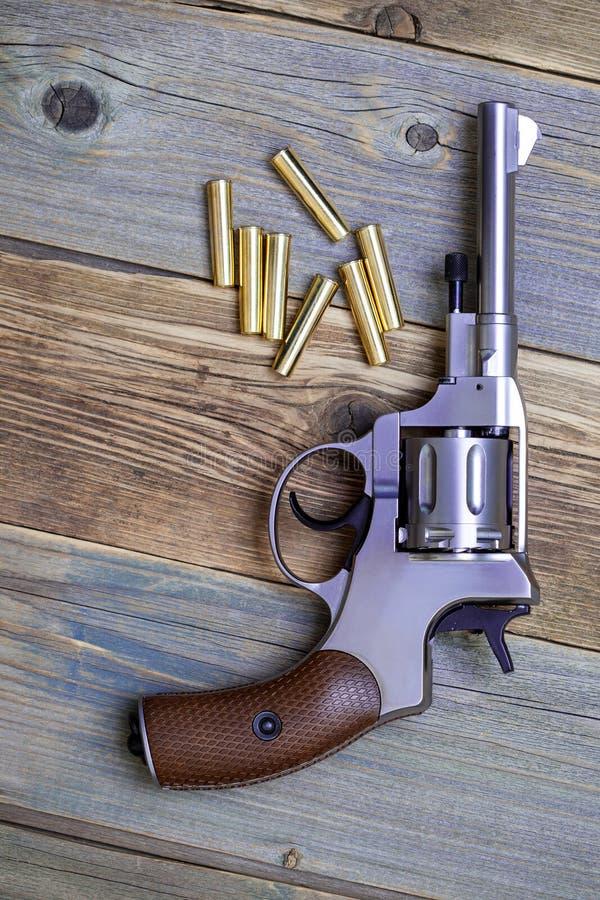 Revolver Nagant de cru avec des cartouches à cylindre rotatif et sept d'or photos stock