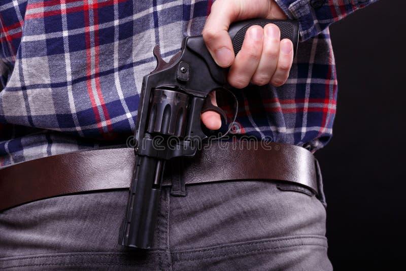 Revolver noir derrière le dos photographie stock libre de droits