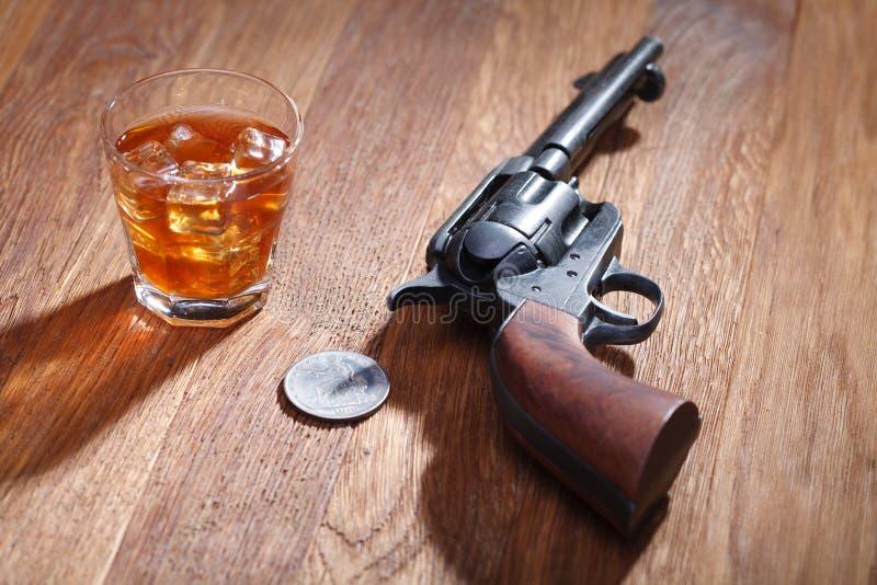 Revolver occidental sauvage avec le verre de whiskey et de glace avec le vieux dollar en argent sur la table en bois photographie stock libre de droits
