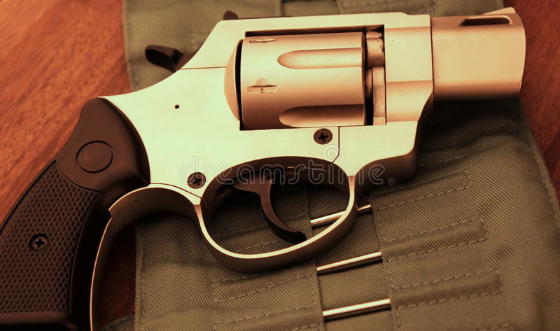 Revolver pistol. On a wood table stock images