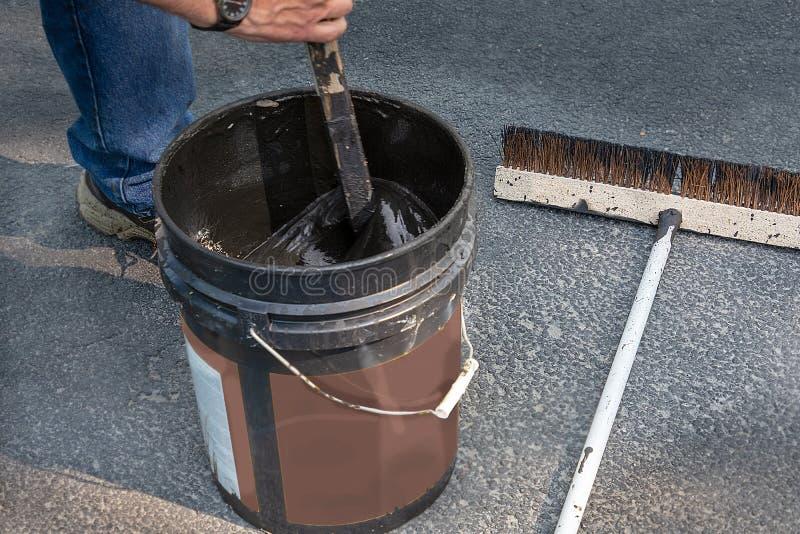 Revolvimiento de la poder de asfalto antes de verter en la calzada fotografía de archivo
