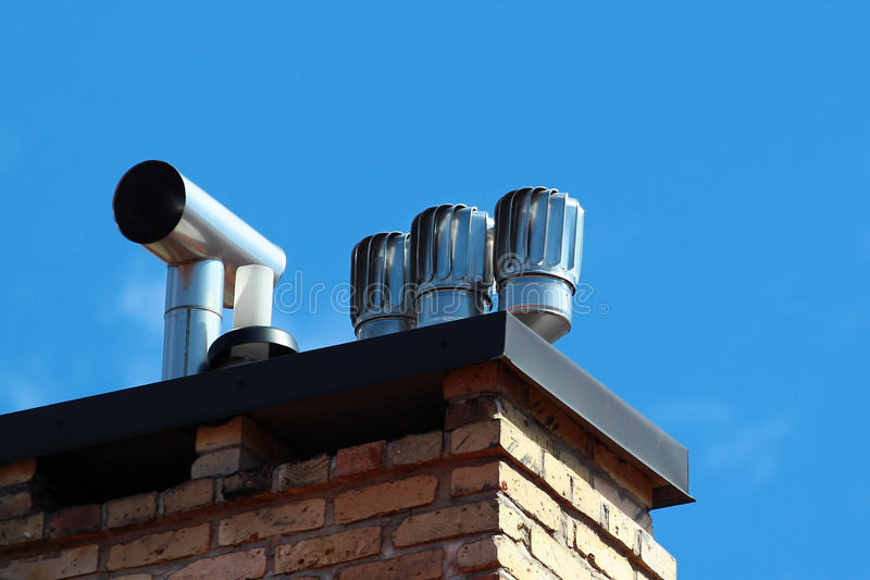 Revolving cowls eradicate downdraught in chimneys. Flues and ducts stock image