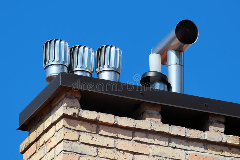 Revolving cowls on a rooftop eradicate downdraught in chimneys stock photo