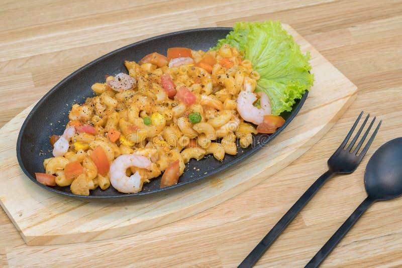 Revuelva a Fried Macaroni con el camarón y los chiles y tomate - pastas del penne, sirviendo en una tabla de madera foto de archivo libre de regalías