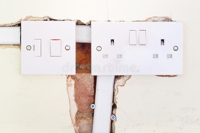 Rewiring British domestic socket. Closeup of a British electrical socket and switch during a domestic rewiring stock photography