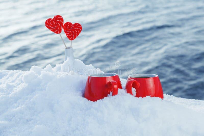 Rewolucjonistka kubki z gorącą herbatą, cukierków serca w śniegu Pinkin na mroźnym dniu na rzecznym lub dennym tle to walentynki  obrazy stock