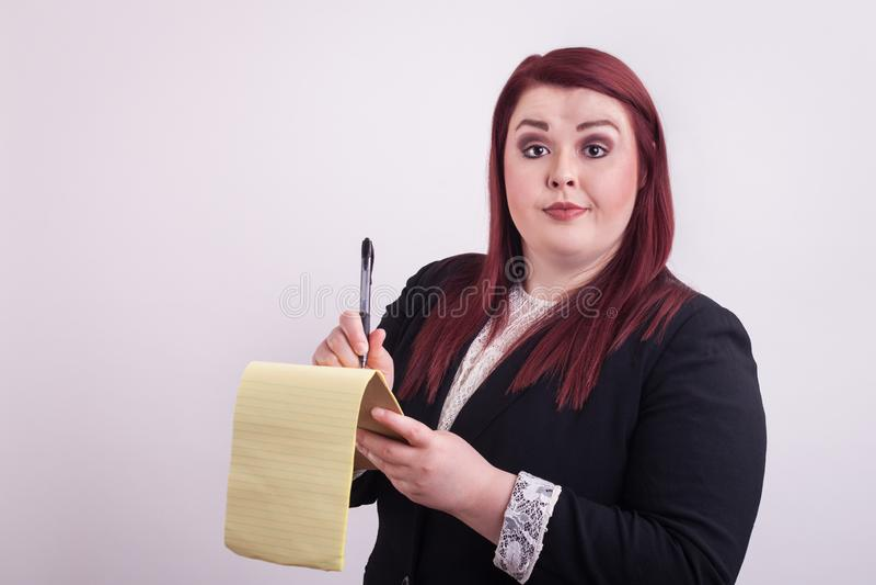Rewolucjonistka przewodził żeńskiego jest ubranym garnitur bierze notatki na żółtym notepad fotografia royalty free