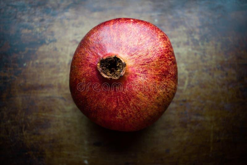 Rewolucjonistki, dojrzałej i soczystej garnet owoc na starym podławym tle, zdjęcia stock
