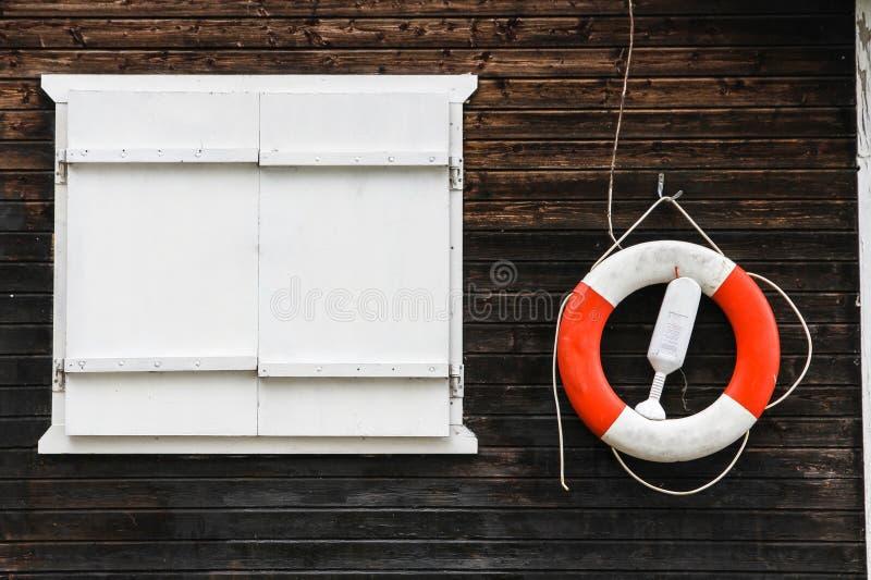 Rewolucjonistki i białego lifebuoy lifebelt z arkanami wiesza od ciemnego brązu malował drewnianą ścianę obraz stock