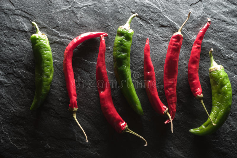 Rewolucjonistki i zieleni chili pieprz na szarość krytykuje zdjęcia stock