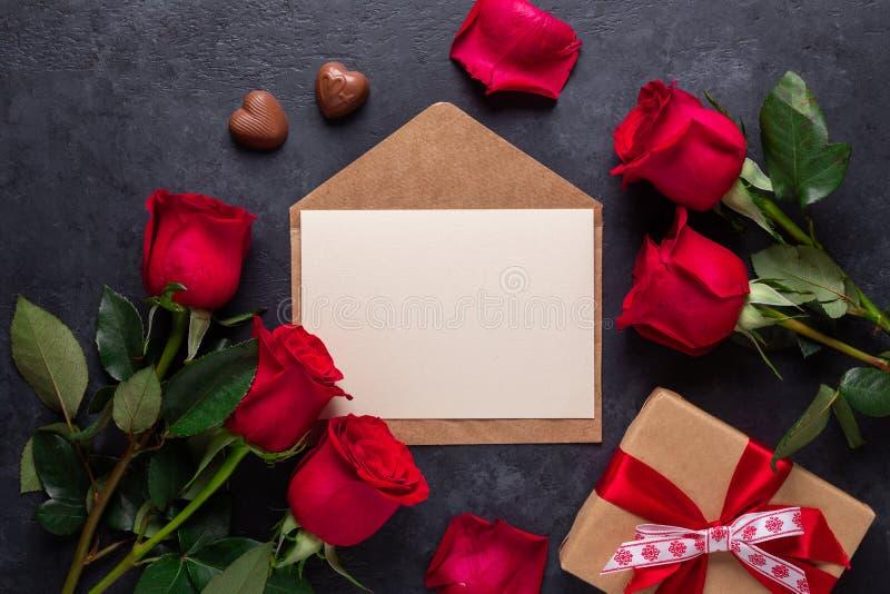 Rewolucjonistki róża kwitnie bukiet, koperta, prezenta pudełko, czekoladowi cukierki na czerń kamienia tła walentynki dnia kartce zdjęcia royalty free