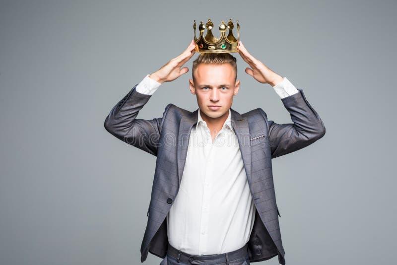 Rey del negocio Hombre de negocios confiado en la situación de la corona aislado en gris fotografía de archivo