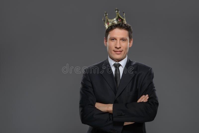 Rey del negocio. Hombre de negocios confiado en la situación de la corona aislado foto de archivo libre de regalías