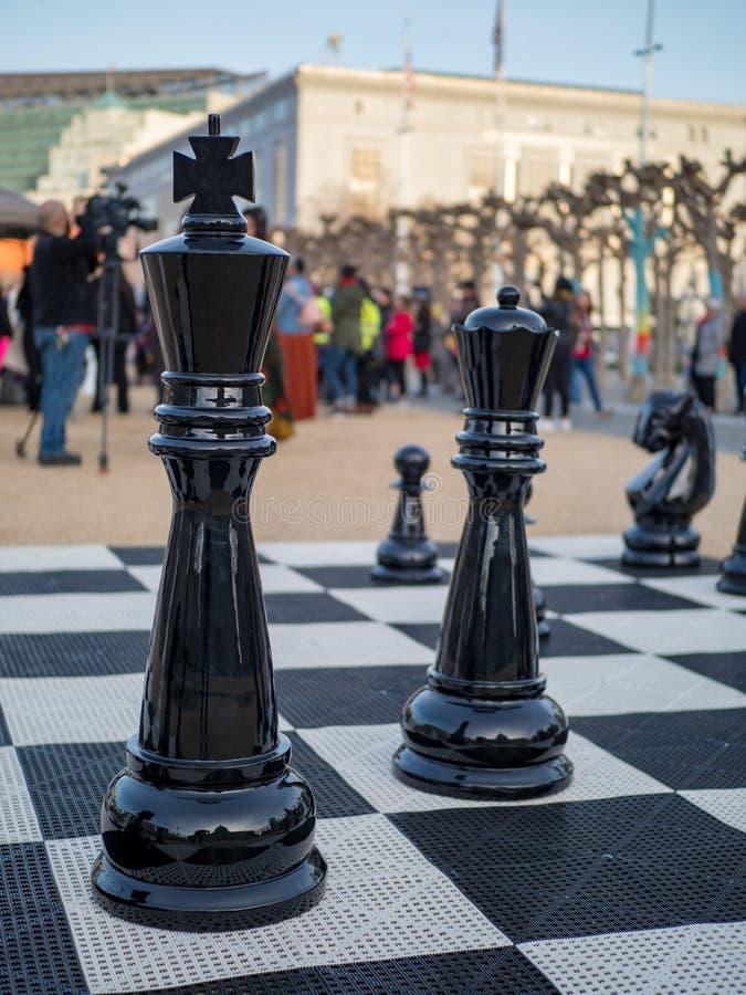 Rey grande, de tamaño natural y pedazos de ajedrez de la reina fotografía de archivo