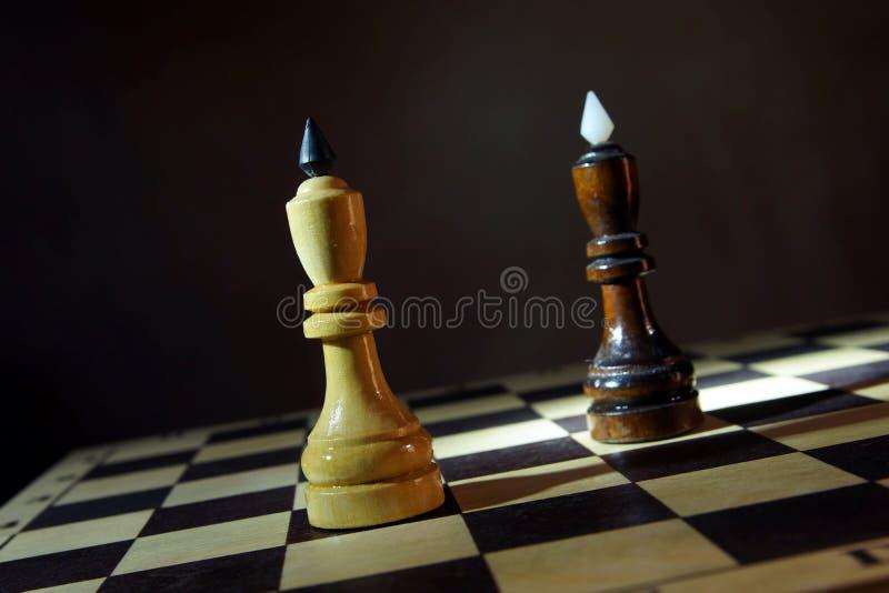 Reyes blancos y negros uno del ajedrez delante de otro Competencia de adversarios iguales fotos de archivo